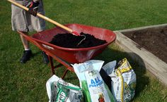 Mix two 40-pound bags of topsoil with one 40-pound bag of compost manure in a wheelbarrow. I like to add a shovelful of slow-release fertilizer to the mix. It can be a little more or less than that—backyard gardening isn't an exact science.  Shovel in the mixture of soil, compost and fertilizer to top off the bed.