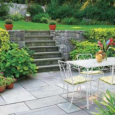 The rough stones in the retaining wall contrast nicely with the smooth bluestone on this sunken patio. | Photo: Randy O'Rourke | thisoldhouse.com