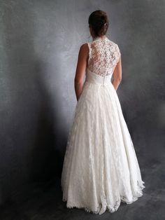 Héléne désirait une robe de mariée classique et romantique avec un grand dos nu.  La robe est en crêpe de soie recourverte de dentelle de Calais à l'ancienne.  la forme bustier affine la taille et laisse les épaules nues.  Le dos nu en dentelle est boutonné entiérement avec des boutons perles