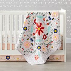 Shop Baja Garden Embroidered Floral Baby Quilt.  Designed to bring homespun style to your nursery, this lavender baby quilt features colorful embroidered flowers in a beautiful decorative pattern.