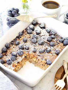 Overhead/Side view of of blueberry baked oatmeal with one piece cut out in a rectangular white baking dish surrounded by flowers, coffee and extra blueberries