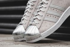 """We've seen the iconic adidas shell toe in an innumerable amount of iterations before, but it's probably fair to say none of them rawk as hard as this one. The """"Superstar 80s Metal"""" pack comes with two premium iterations of the sneaker. The two sneakers feature a light grey ostrich leather upper with silver metallic toecap …"""