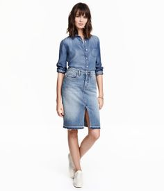 5-pocket, knee-length skirt in washed stretch denim with distressed details, slit at front, and raw, frayed hem.