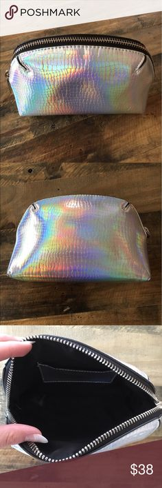 Topshop Large Half Moon Hologram Makeup Bag Beautiful one of a kind Topshop Hologram Makeup Bag. I bought this in Denmark so you will not find it in the states. Iridescent faux-croc textured makeup pouch from Topshop is truly eye-catching!  Has a small pocket inside. Gently used, see pics for minor wear. Topshop Bags Cosmetic Bags & Cases