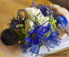 Royal Blue Wristlet with Bling. Made this for a royal blue dress. Curled wire and wired ribbon with roses delphiniums and rhinestone bling. http://gardenhouseliving.com
