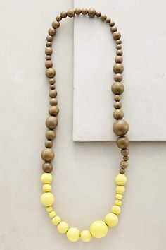 Our beautiful Dipped Neon Yellow Necklace in sustainable mango wood. Available now from anthropologie.com