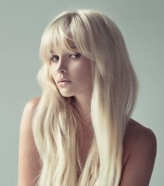 Long blonde hair with wispy full front bangs. Great hairstyle for making a round face appear more oval.