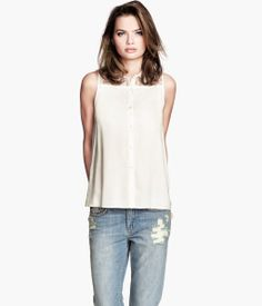 Sleeveless blouse with lace cut out.