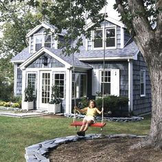 Cottage home with vestibule brightened by door & windows with lots of panes, white shutters with cutout lighthouse motifs, window boxes and shingle siding. Love the tree with slate edging & charming swing!