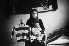 """'Nothing replaces the loss of a son, not even another son.'  Safia Abo Zour, 25, holds her five-month-old baby, Mohammed, with one hand and holds with the other the sweater her older son, also named Mohammed, wore the last time he went to kindergarten. Mohammed had just turned four years old when he was killed during the second war in Gaza in 2011 after an airstrike on his family's house in the Al Zaitoun neigborhood. Safia named her new baby after his brother."" -- Eman Mohammed"