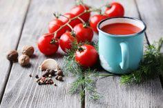 マグカップに入ったトマトジュースと房がついたトマト