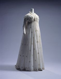 Dress (round gown)c. 1795-Italy White muslin one-piece dress with long train; blue and brown cotton and silver embroidery of plant patterns; shirring at top of front; lace decoration around neckline