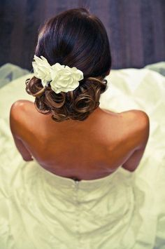 black curly wedding updo with hair flowers