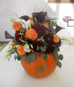 fall arrangement in pumpkin. Pumpkins mini pumpkins and gourds make great containers. Like the color combo of orange dahlias and dark greenery
