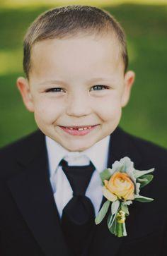 adorable little man with pretty bout! - photo by Ariel Renae - http://ruffledblog.com/peach-and-gold-georgia-wedding/