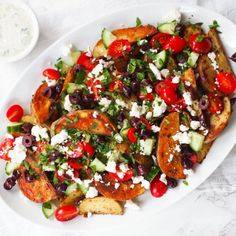 These Greek loaded baked potato wedges are topped with cherry tomatoes, feta, parsley, cucumber and kalamata olives.