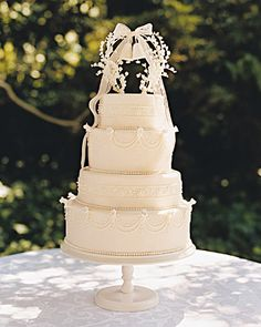 A wedding bell cake topper made with quilling paper and framed by vintage millinery lily-of-the-valley buds