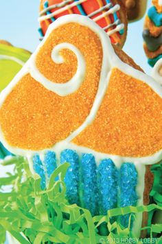 This cupcake cookie design sparkles with shimmery sanding sugar! Pipe the  outline and the details first, and allow them to harden. Next, flood the cookie with icing in sections, one color at a time.