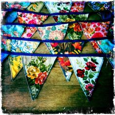 DIY Sewing project / idea. Flag banner with lots of color/floral! Triangles sewn or serged together & binding.