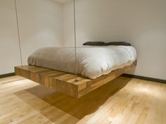 Wooden Oak Of Suspended Birdseye Bed In Modern Small Bedroom Design With White Bedlinen Black Pillows Also Wooden Laminate Flooring And White Wall Paint