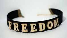 Finish off your look with this super cute FREEDOM Letter Choker necklace.Take your outfit to the next level with this black wooden choker. * Length: 30 cm * Width: 2 cm * Chain link whit lobster clasp * Letters material: wood * Band material: elastic Available in black,red and white color