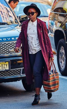 Lupita Nyong'o is ready for fall – gotta love her Marsala red trench coat, felt fedora and chunky tortoise cat-eye sunnies!