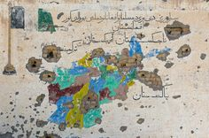 A bullet-riddled map of Afghanistan, painted on a wall of an abandoned Canadian-built school in Zharay district of Kandahar province, southern Afghanistan, on June 9, 2012.
