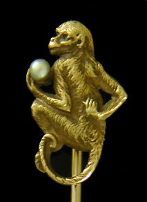 A monkey contemplates a small pearl while nonchalantly scratching his back.  Note the rich details of the monkey's fur and his bemused expression.  Beautifully crafted in 14kt gold,  circa 1900.