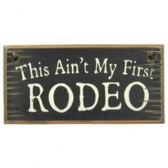 Show your sense of humor with this black vintage 'This Ain't My First Rodeo' Wood Sign. It would look great in any western-themed home, office or man cave⎜Open Road Brands