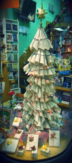 Christmas tree made of damaged books pages. Bookstore window display - Paraguay