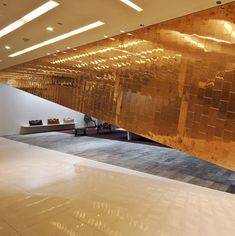 A diagonal wall clad in copper plates partially hides the interior of this boutique in Tenjin Fukuoka, Japan.