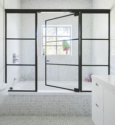 These steel framed windows and door give this shower a luxe, industrial edge and…