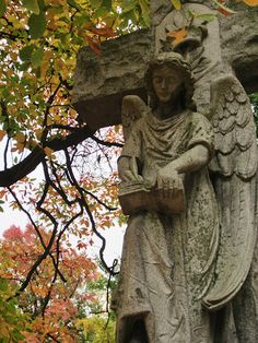 Angel scribe in autumn trees at Woodland Cemetery and Arboretum in Dayton, Ohio.