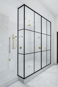 Black and white bathroom decor - crittal style shower screen in a marble tiled bathroom