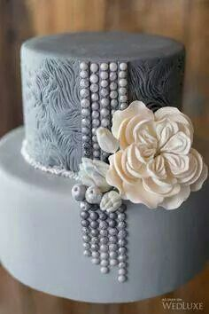 Silver grey tier cake with textured top tier, bead details and ivory flowers.
