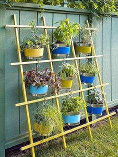 2x2 lumber formed into a nine square lattice configuration makes the framework for a hanging basket focal point. This idea utilizes inexpensive galvanized buckets as planters. The buckets could be stenciled, striped, polka dots, etc. Or any hanging planter could be used as long as the hanger allowed it to be centered in the square openings.