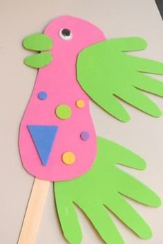 Parrot Stick Puppets using craft foam, jumbo craft sticks, and wiggly eyes. Body of the parrot was made from tracing their foot and the wings and tail feathers were their hands.+