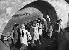 Palestinian  women and children draw water from Mary's well in Nazareth, Palestine, on Dec. 7, 1946, the ancient spring which legend relates supplies water for Mary, Joseph and Jesus.