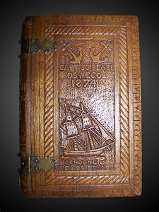 This exceptionally rare piece of sailors' folk art has its' cover carved with the name 'Capt. J C Pease, Oswego, 1874' over a carved depiction of a Schooner named 'Schooner Delos Dewolf.' The spine is carved with the name of the book 'The American Cruisers Own Book.' The back cover is carved with a schooner and a steamer. Ornate brass hinges. A museum quality piece.