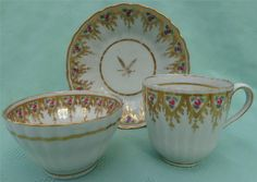 """New Hall Trio c.1785  This is a lovely late 18th century reeded ogee shape porcelain trio consisting of a tea bowl, coffee can and saucer manufactured by New Hall c.1785.  They are unmarked but are illustrated in David Holgates book """"New Hall"""" (1987), color plate L.  They are decorated in pattern no. 83, made up of a beautiful hand painted border of pink roses and gold swags."""