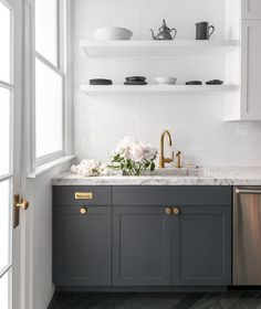 Dark gray kitchen cabinets accented with aged brass knobs, vintage ...