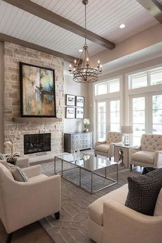 Beautiful living room features a ceiling lined with taupe wood beams over a pair of ivory linen nailhead chairs facing a pair of ivory tufted chairs across from a rectangular mirrored coffee table atop a blue trellis rug illuminated by an iron candelabra chandelier.