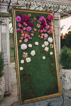 Brides.com: . Imagine exchanging vows in front of a giant moss and flower wall — the bright blooms really pop against the woodsy framed backdrop. Created by Oleander.