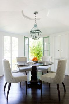 The breakfast room is bright and airy with green windows that are original to the house. The table and chairs are custom pieces designed by Hodges and covered in a Rose Tarlow linen. Accenting the sculptural ceiling is a chandelier from the Urban Electric Company.