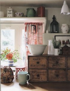 English cottage kitchen - the neat crate-type storage, the mismatched china, flowers, teacozy and curtain - charming -