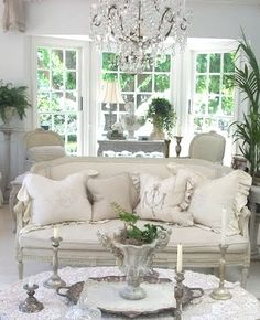sofa and pillows and candlesticks and chandelier