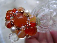Nicht nur für strahlende Gemüter ist dieser Ring in leuchtenden warmen Farben, diesem dunklen orange mit den schimmernden Süßwasserperlen  ein gute La