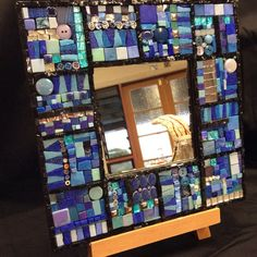 This beautiful mosaic mirror frame has been carefully hand-crafted from many different types of tessera, all in vibrant shades of blue. Measuring 30x30cms, this gorgeous, one-of-a-kind frame will add a real sense of the eclectic to any room. Crafted from smalti, ceramic tile, glass tile, stained glass, buttons, vitreous tile, millefiori (the Italian glass of a million flowers), mirror and metallic foil tiles in a patchwork quilt effect, this beautiful mirror is a truly unique piece of…