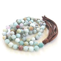 Give your spirit freedom to take flight with this Amazonite and leather tassel Mala from True Nature Jewelry. Custom designed in majestic detail, it features an colorful arrangement of Amazonite gemstones. The effect is earthy, yet glamorous. Amazonite is a calming stone believed to dispel negative energy and improve confidence and Rose Quartz for inner peace and a building a strong sense of self-worth. This nature inspired Mala is made complete by the leather tassel that dangles from the…