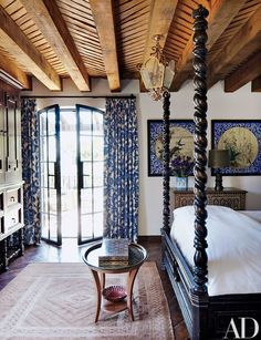 In a guest room, the house's blue-and-white motif continues with curtains made of a Kravet fabric and, on the adjacent wall, two antique ceiling panels from a Japanese temple | archdigest.com